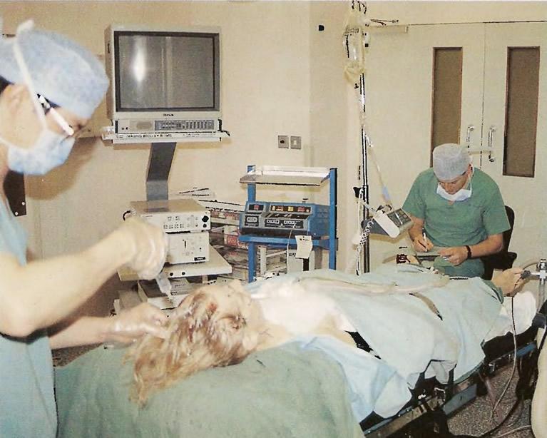 Хирург зачесывает волосы назад и вводит местный анестетик в область лица