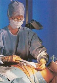 Медсестра наклеивает ленту на шов и на дренажные трубки