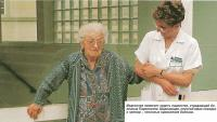 Медсестра помогает ходить пациентке, страдающей болезнью Паркинсона