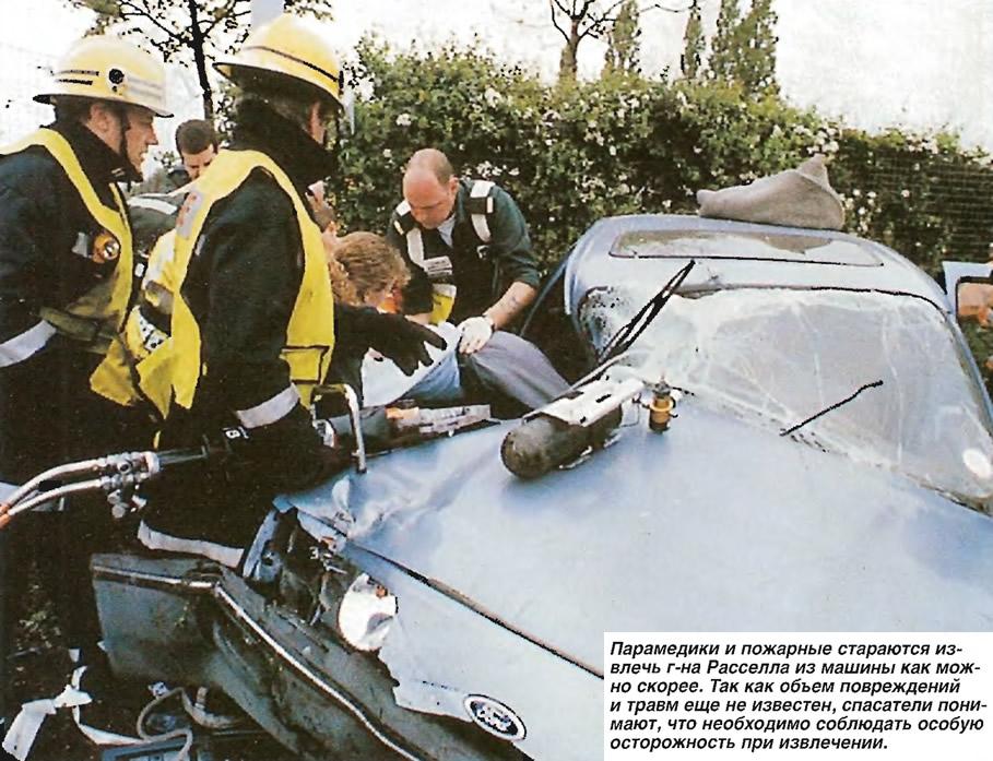 Парамедики и пожарные стараются извлечь г-на Расселла из машины