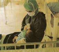 Ребенка с врожденной недостаточностью в стерильных условиях кормит медсестра