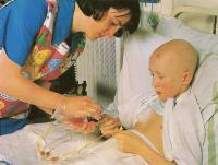 Сестра проводит внутривенную химиотерапию мальчику с лейкозом